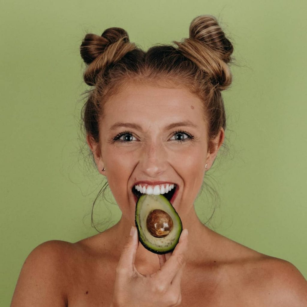 Happy woman biting into an avocado - Keto Diet vs Metabolic Balance