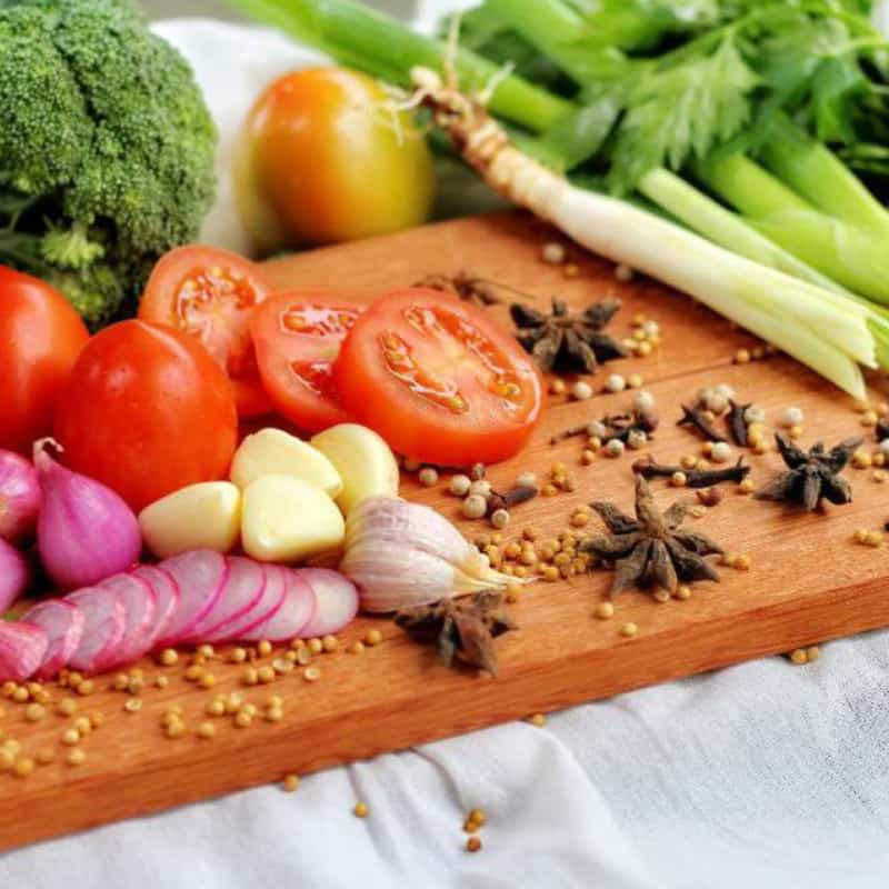 Cutting board layered with spices aand fresh vegetables