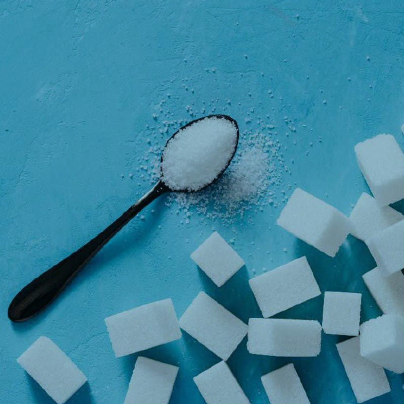 Teaspoon of white sugar on blue table and scattered sugar cubes - learn how to kick sugar and feel great