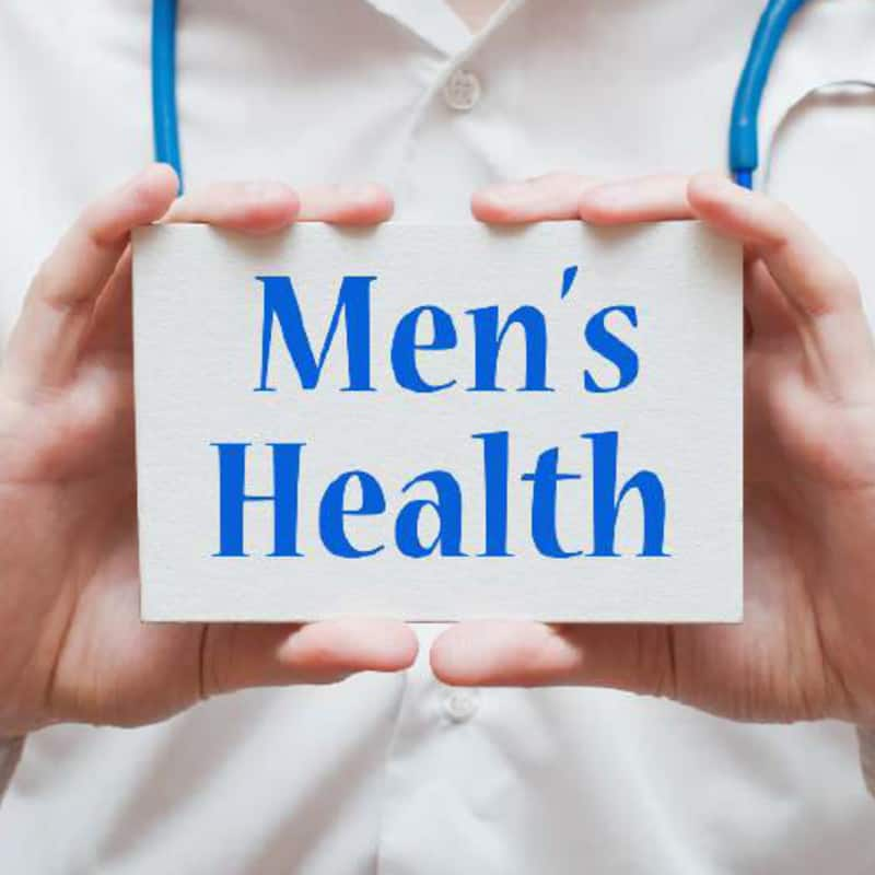 """A man holding a small sign in front of him saying """"Men's Health"""""""