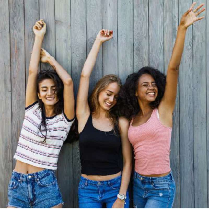 Three young women looking very happy with their hands in the air