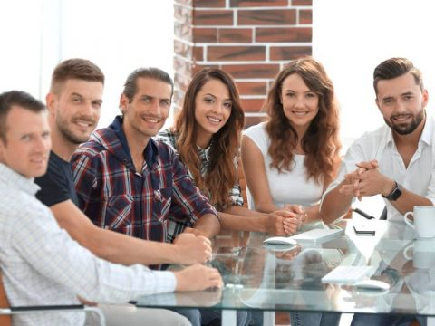 Group of young happy business people around a glass table attending a Workplace Nutrition Workshop